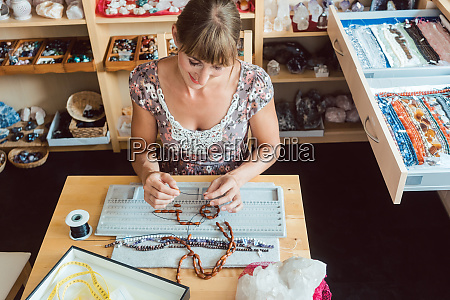 mulher trabalhando em um colar de