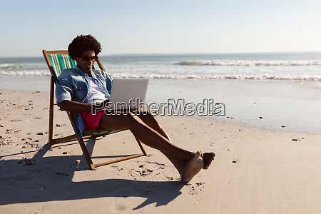 man using laptop while relaxing in