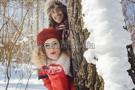casal brincalhao na neve escondido atras