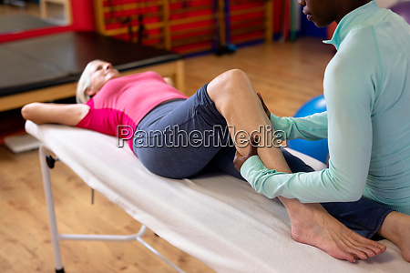 fisioterapeuta faz massagem nas pernas para