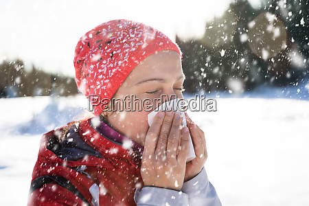 woman blowing her nose with a