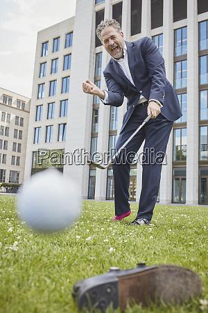 feliz empresario maduro jogando golfe no