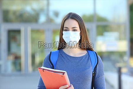 estudante usando uma mascara andando em