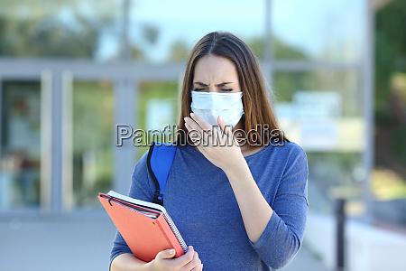 estudante doente com uma mascara tossindo
