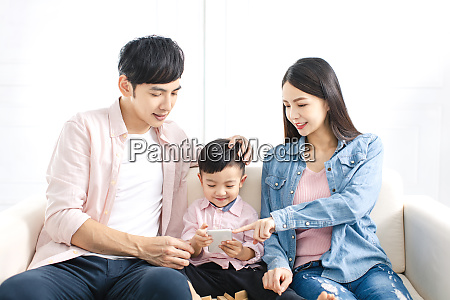 familia feliz assistindo o telefone inteligente