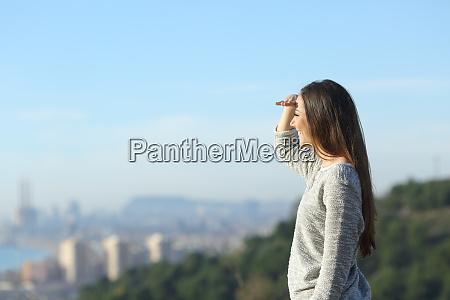 happy woman looking at horizon protecting