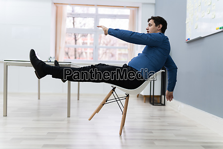 man falling on chair in office