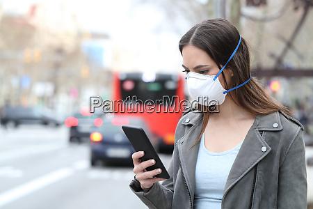 mulher com mascara usando telefone com
