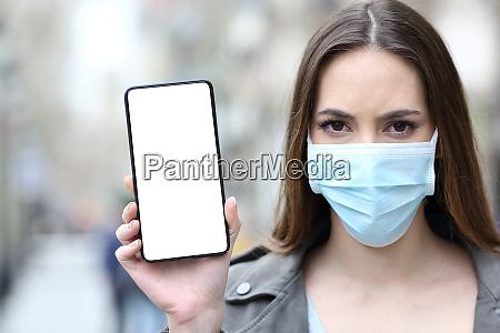 mulher com mascara protetora mostrando tela