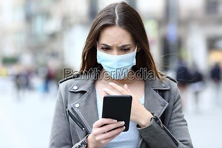garota assustada com mascara lendo noticias