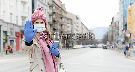 mulher usando mascara corona dando sinal