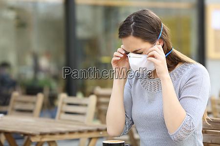 mulher colocando mascara protetora no terraco