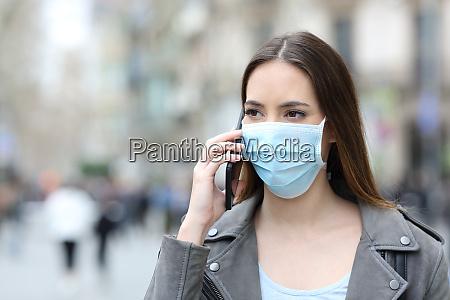 mulher com mascara falando ao telefone