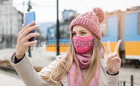 mulher fazendo sinal de vitoria fazendo