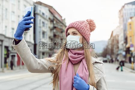 mulher com mascara medica e luvas