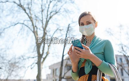 mulher usando seu telefone usando mascara