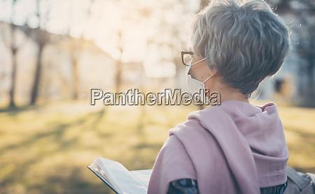 senhora idosa com mascara facial lendo