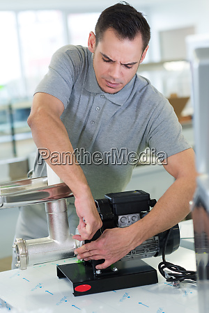 man repairing an electrical meat mincer