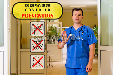 male doctor in hospital corridor showing