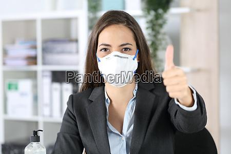 executivo com mascara com polegares para