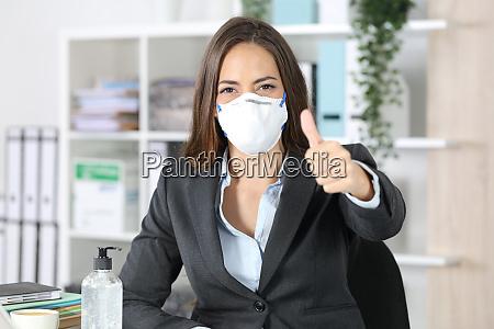 executivo usando mascara com polegares para