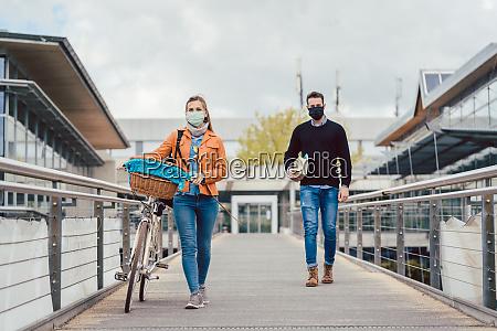 estudantes no campus universitario usando mascaras