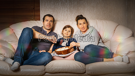 family sitting on sofa and watching