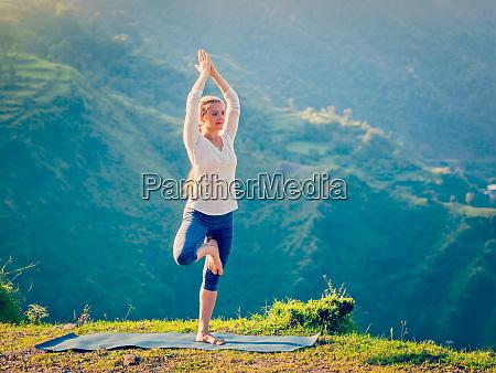 woman doing yoga asana vrikshasana tree