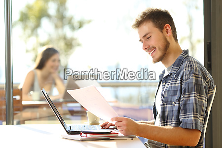 happy student works on laptop in