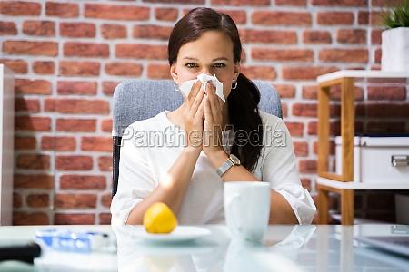sick business employee or worker sneezing