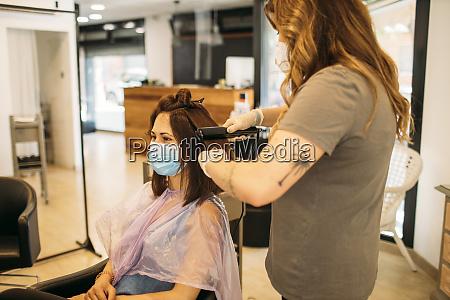 cabeleireira cortando cabelo em um cabeleireiro