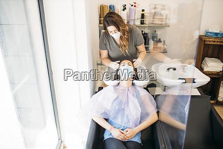mulher com mascara recebendo cabelo lavado