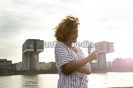 mulher adulta media segurando garrafa de
