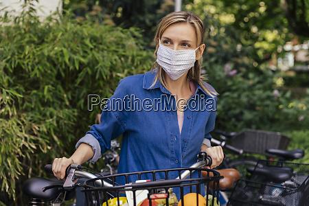 mulher usando mascara facial com bicicleta
