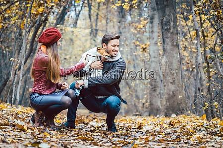 mulher e homem acariciando o cao