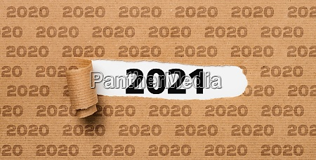 papel rasgado revelando o numero 2021