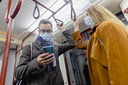 pessoas usando telefone no trem usando