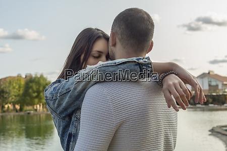 casal jovem sereno e afetuoso abracado