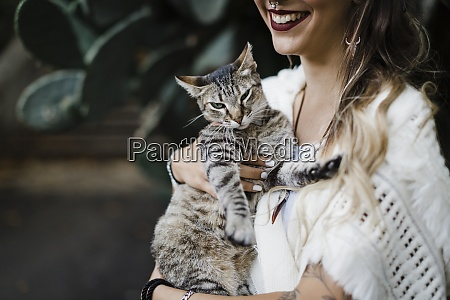 mulher sorridente segurando gato enquanto esta
