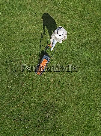 mulher com cortador de grama em