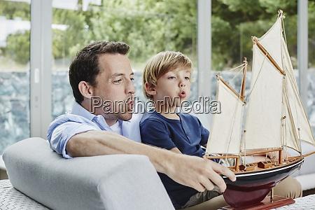 pai e filho soprando barco de