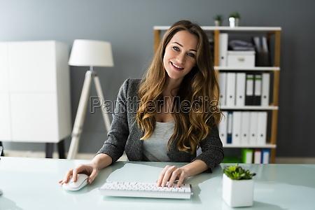 feliz funcionaria profissional usando computador